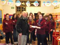 Lion Ron presenting the cheque to the Ottery Guides in their Hoodies