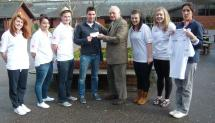 Lion Ron Webb presenting cheque and named T shirts to Andy Taylor Head PE and Sports