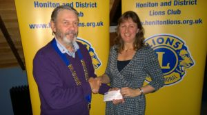 Lion president John awarding Laura with £250