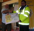 Kevin Lee accepting the cheque for £500 from Lion President Brian Richards