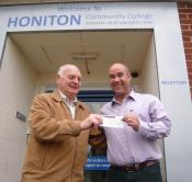 Lion Ron Webb presenting cheque for £100 to Honiton College FD Gary Wills